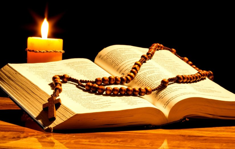 picture of a candle rosary and bible on a black background